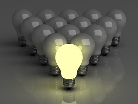 Leadership concept, One glowing light bulb standing in front of unlit incandescent bulbs with reflection on dark background photo
