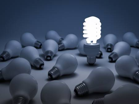 different idea: Eco energy saving light bulb, one glowing compact fluorescent light bulb standing out from the unlit incandescent light bulbs or Individuality concept