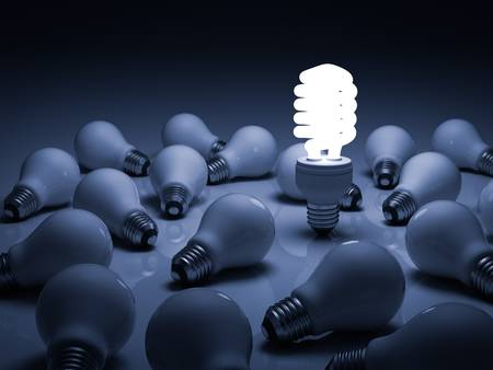 Eco energy saving light bulb , one glowing compact fluorescent lightbulb standing amongst the unlit incandescent bulbs with reflection photo