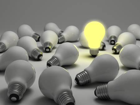 Una bombilla de luz incandescente entre las bombillas incandescentes sin luz en el fondo blanco Foto de archivo
