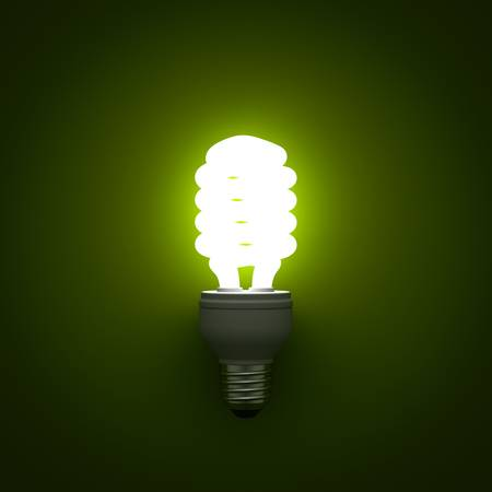 Energy saving compact fluorescent light bulb glowing on green background photo