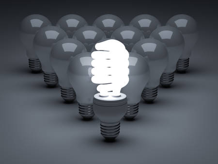 Leadership concept, One glowing Eco energy saving light bulb standing in front of unlit incandescent bulbs over dark background photo