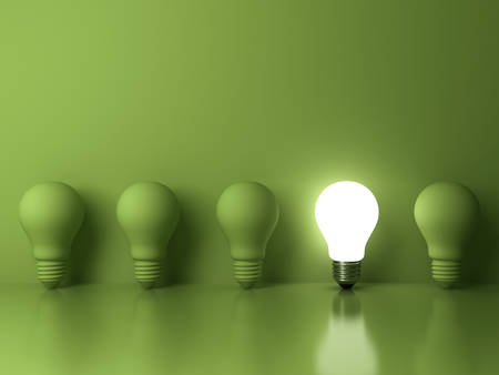 One glowing light bulb standing out from the unlit incandescent bulbs on green background with reflection , The business concept and individuality concept . 3D rendering. Stock Photo