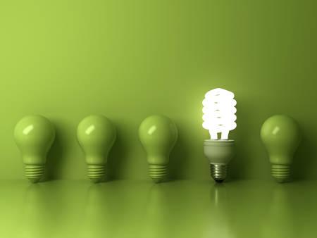 Energiesparende Glühlampe Eco, eine glühende kompakte Leuchtstoffglühlampe, die heraus von der unlit Glühlampereflexion auf grünem Hintergrund, von Individualität und von unterschiedlichem Konzept steht. 3D-Rendering.