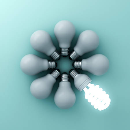 Eco energy saving light bulb , one glowing fluorescent lightbulb standing out from unlit incandescent bulbs on green background , individuality and different creative ideas concepts . 3D rendering.