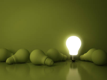 One glowing light bulb standing out from the dead incandescent bulbs on green background with reflection , individuality and different creative idea business concepts . 3D rendering.