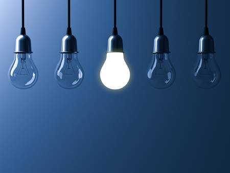 One hanging light bulb glowing different and standing out from unlit incandescent bulbs with reflection on dark blue background , leadership and different business creative idea concept. 3D rendering.
