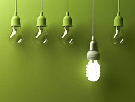One hanging energy saving light bulb glowing different stand out from unlit incandescent lightbulbs with reflection on green background , leadership and different creative idea concept . 3D rendering. Stock Photo
