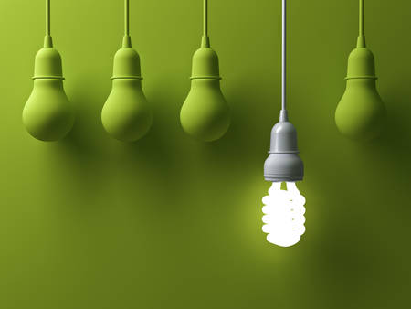 power of thinking: One hanging energy saving light bulb glowing different stand out from unlit incandescent lightbulbs on green background with shadow , leadership and different creative idea concept . 3D rendering.