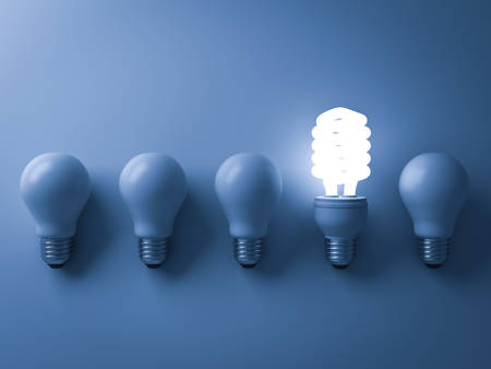 invent: Energy saving light bulb , one glowing compact fluorescent lightbulb standing out from unlit incandescent bulbs on blue background , individuality and different creative idea concepts . 3D rendering. Stock Photo