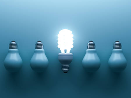 different thinking: Energy saving light bulb up , one glowing fluorescent lightbulb standing out from unlit down incandescent bulbs on blue background , individuality and different creative idea concepts . 3D rendering. Stock Photo