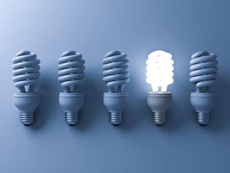 Bombilla ahorro de energía, una bombilla fluorescente compacta que brilla intensamente que se destaca de bombillas apagadas en fondo azul, individualidad y diversos conceptos creativos de la idea. Representación 3D Foto de archivo - 76191839