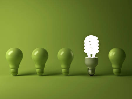 divergence: Eco energy saving light bulb , one glowing compact fluorescent lightbulb standing out from unlit incandescent bulbs reflection on green background , individuality and different concept . 3D rendering.