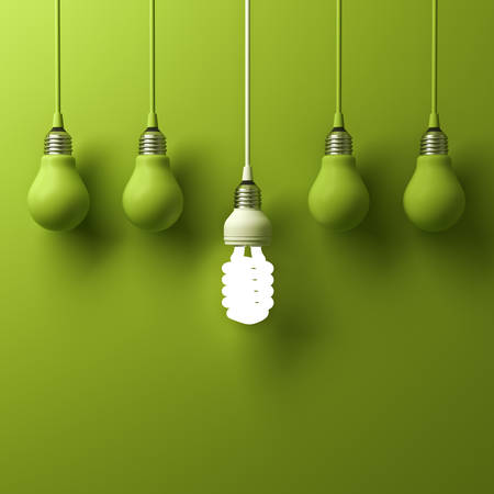 power of thinking: One hanging energy saving light bulb glowing different standing out from unlit incandescent bulbs with reflection on green background, leadership and different creative idea concept. 3D rendering. Stock Photo