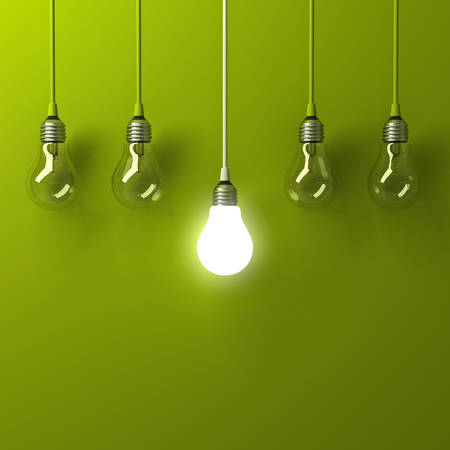 One hanging light bulb glowing different and standing out from unlit incandescent bulbs with reflection on green background , leadership and different business creative idea concept . 3D rendering.