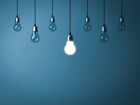 One hanging light bulb glowing and standing out from unlit incandescent bulbs on dark cyan background. 3D rendering.