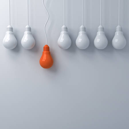 Think different concept , One hanging orange light bulb standing out from the dim unlit white light bulbs on white wall background , leadership and individuality creative idea concepts . 3D rendering.