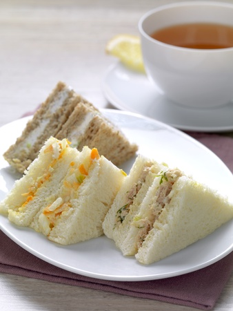 a variety of club sandwiches served in a white plate with a cup of hot tea