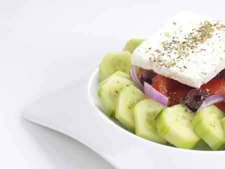 a traditional greek salad with feta cheese,tomatoes,cucumber,onion slices,olive slices,oregano and virgin olive oil Stock Photo - 8664318