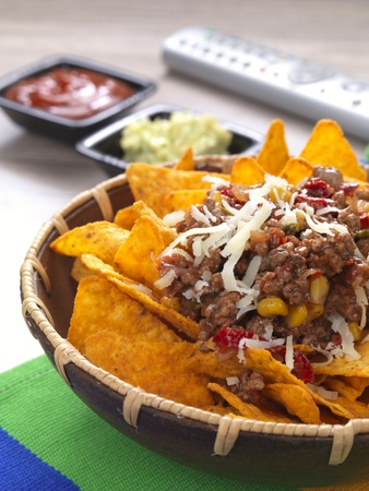 a bowl with spicy tortilla chips served with minced meat and cheese