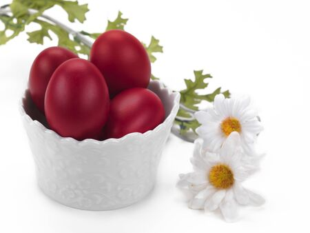 a porcelain bowl full of red easter eggs with a flower decoration on a white background