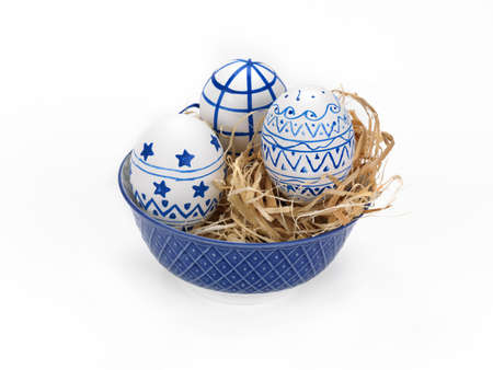 easter eggs in a porcelain bowl on a white background photo