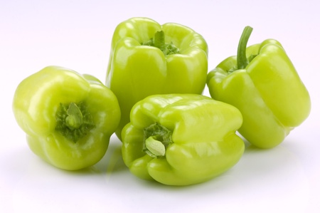four green bell peppers on a white background