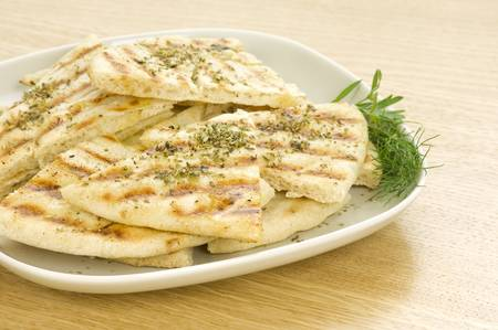 greek grilled pittas sliced and poured with olive oil and oregano Stock Photo - 9212511