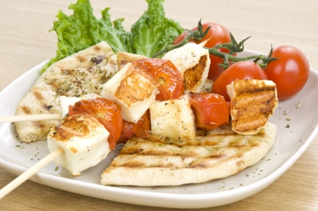 haloumi: a grilled souvlaki made of cyprian cheese(haloumi) and cherry tomatoes, served with greek pitta