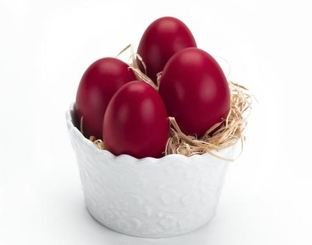 Eine weiße Porzellan Schüssel voller red Ostereier Standard-Bild - 9212497