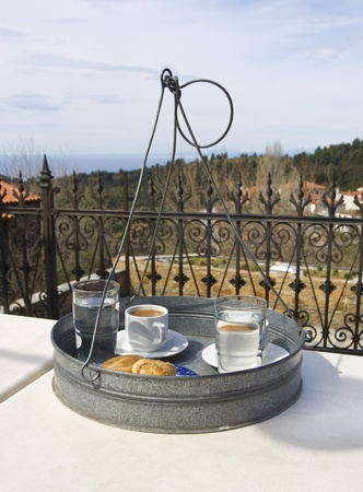 a traditional serving tray with greek coffee and cookies on a table in a veranda in North Greece Stock Photo - 9212487