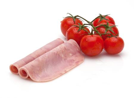 two slices of boiled ham with cherry tomatoes Stock Photo