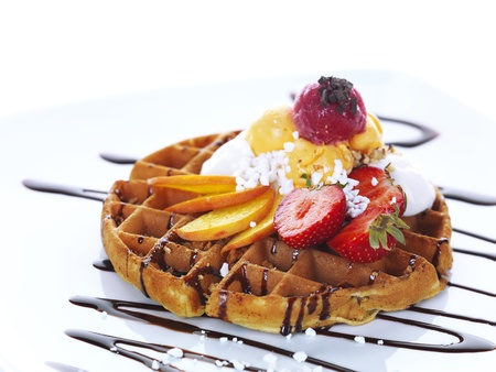 delicious home-made waffle with some slices of fresh peach and strawberries,fruit flavoured ice cream and chocolate sauce