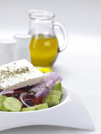 a traditional greek salad with feta cheese,tomatoes,cucumber,onion slices,olive slices,oregano and virgin olive oil photo