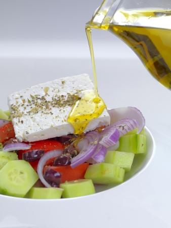 een traditionele Griekse salade met feta kaas, tomaten, komkommer, ui, olijf plakjes, oregano en olijfolie Stockfoto
