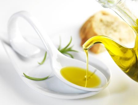 bottle pouring virgin olive oil in a porcelain spoon Standard-Bild