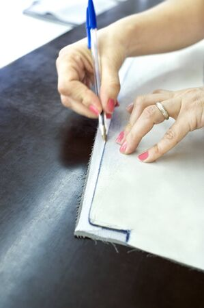 tailor suit: womans hands drawing a fabric in a tailors shop Stock Photo