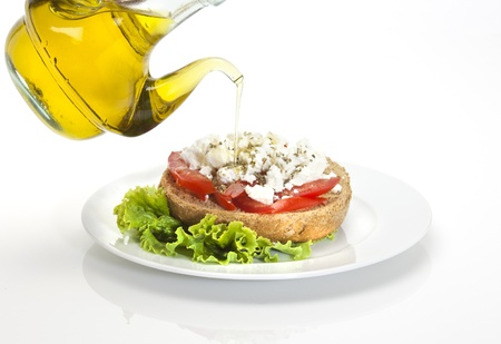 lunch break: typical Cretan plate called ntakos, a slice of barley bread , cubes of tmato, goat cheese, virgin olive oil and herbs Stock Photo