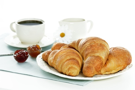 croissants,marmelades and coffee on a light blue table cloth