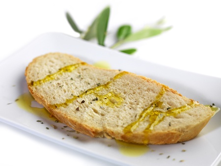 cooking oil: pouring olive oil on a slice of bread with oregano