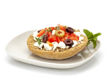 cretan greek  typical plate with a slice of roasted barley bread, goat cheese, olives, tomato, herbs and olive oil