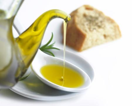 スプーン、オレガノとパンのスライスにオリーブ オイルを注ぐ