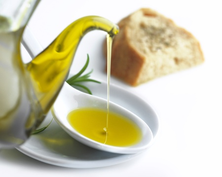 오레가노와 숟가락과 빵 조각에 올리브 기름을 붓는