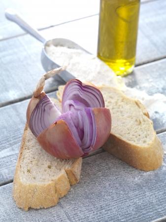 Zwiebel auf einem Stück Brot, eine Kugel aus Weizenmehl und eine Flasche Olivenöl auf einem Holztisch Standard-Bild - 25365013