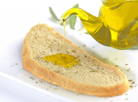 pouring virgin olive oil on a slice of bread with oregano photo