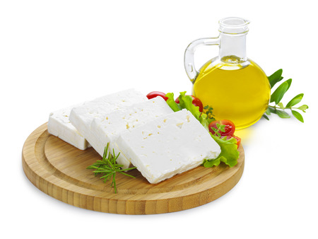 feta cheese(Greek cheese) slices on a wooden serving board decorated with fresh vegetables and a bottle of olive oil