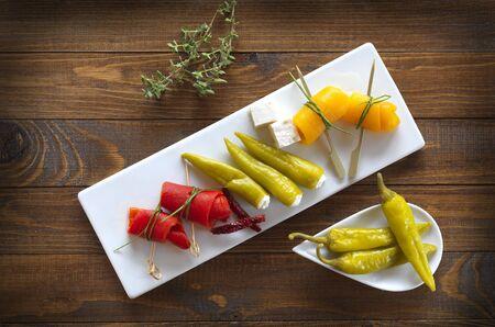 Eine Mischung aus Antipasti, mariniert und gefüllte Paprika auf einem hölzernen Hintergrund Standard-Bild - 48631339