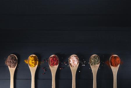 especias: cucharas de madera con especias en un fondo oscuro