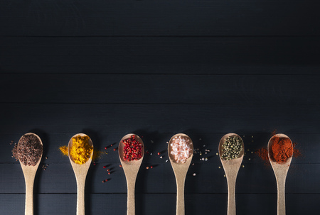 wooden spoons with spices on a dark background