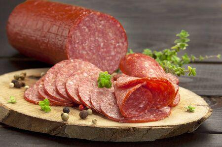 salami: reducido a la mitad en rodajas de salami de pavo que se presentan en un trozo de madera con tomillo y pimienta molida